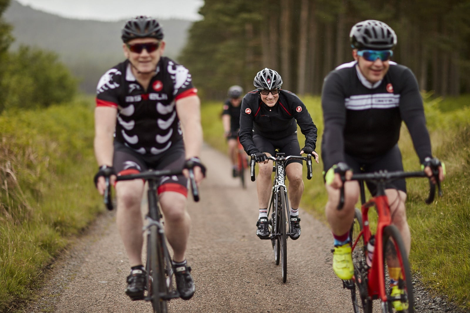 Four men riding road bikes on a road in the National Park