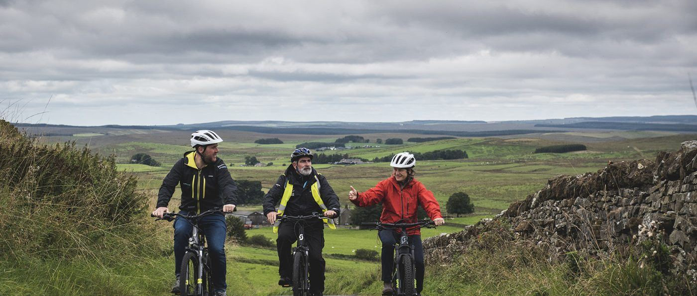three people riding E-bikes near Hadrian's Wall