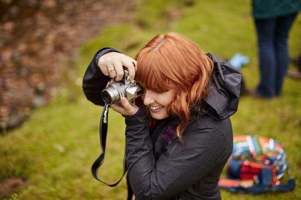 A young woman taking a photograph with a camera