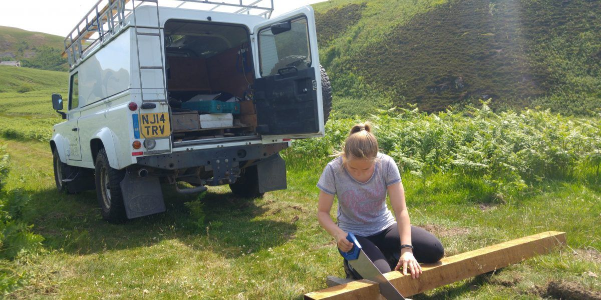A young volunteer sawing wood close to a national park vehicle.