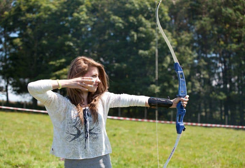 a young woman firing an arrow from a bow
