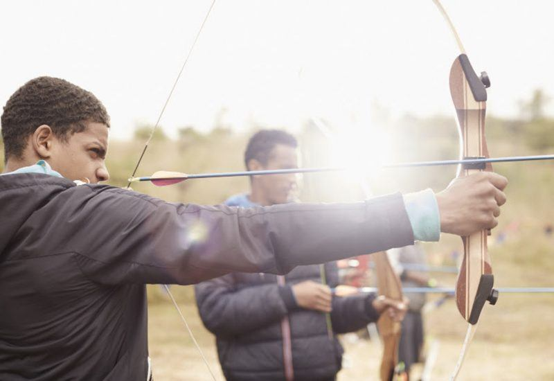 a group of young people with bows and arrows