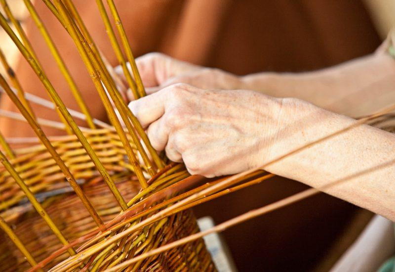 hands weaving willow into a basket