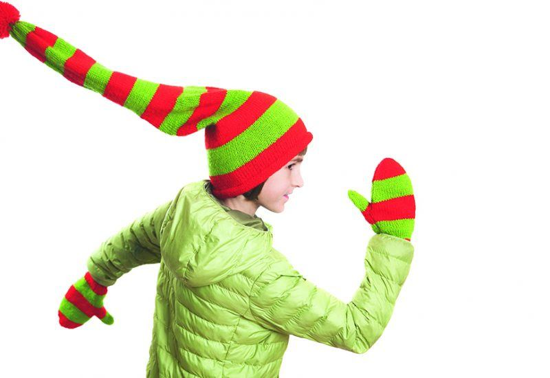a young girl with christmas themed hat and gloves on running