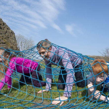 family crawling under a net at walltown with the walltown warrior logo shown