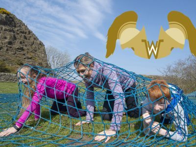 a family crawling under a net at walltown with the walltown warrior logo shown