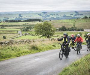 Three people riding Ebikes near Hadrian's Wall