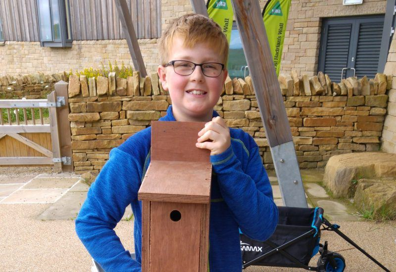 Young participant holding a bird box during Ranger School Week