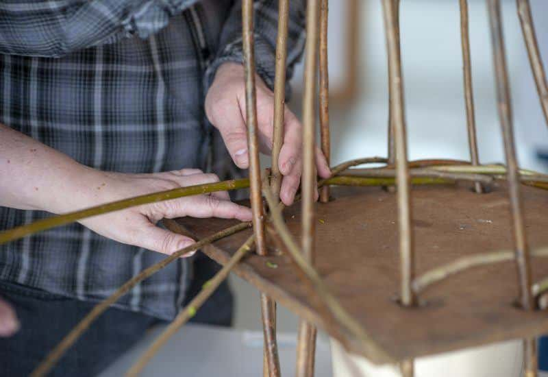 close up of hands making ornaments with willow