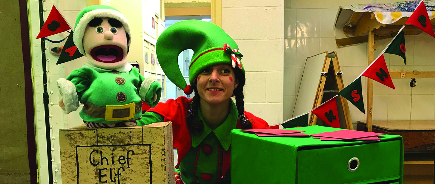 A performer dressed as an elf with an elf puppet