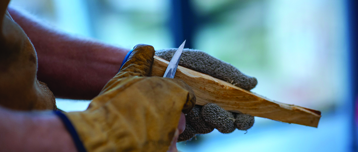 close up of a man's hands carving a wooden spoon