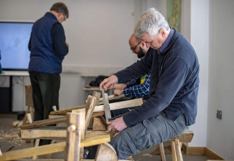 two adults planing wood
