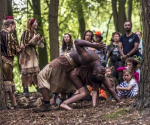 An audience in woodland watch a performance of Told in Gold