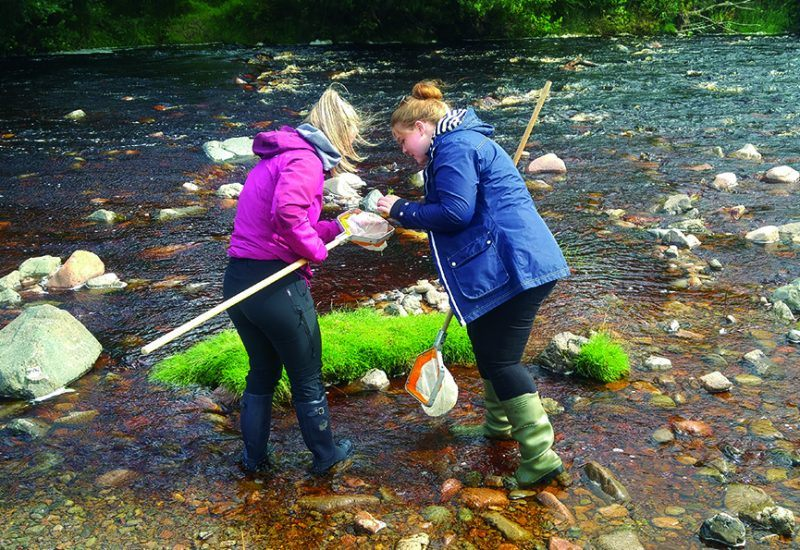 Two young women pond dipping in the National Park
