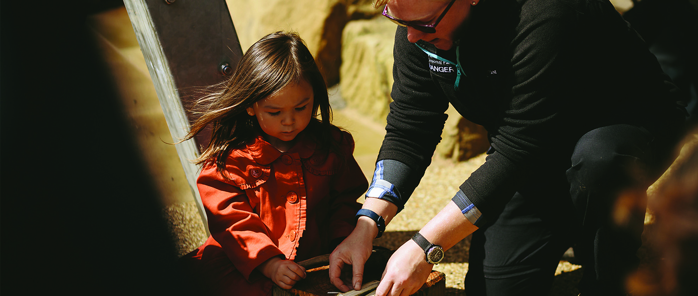 A National Park Ranger making a wooden whistle with a young child