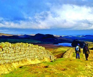 Walkers walking alongside Hadrian's Wall at Winshield Crags