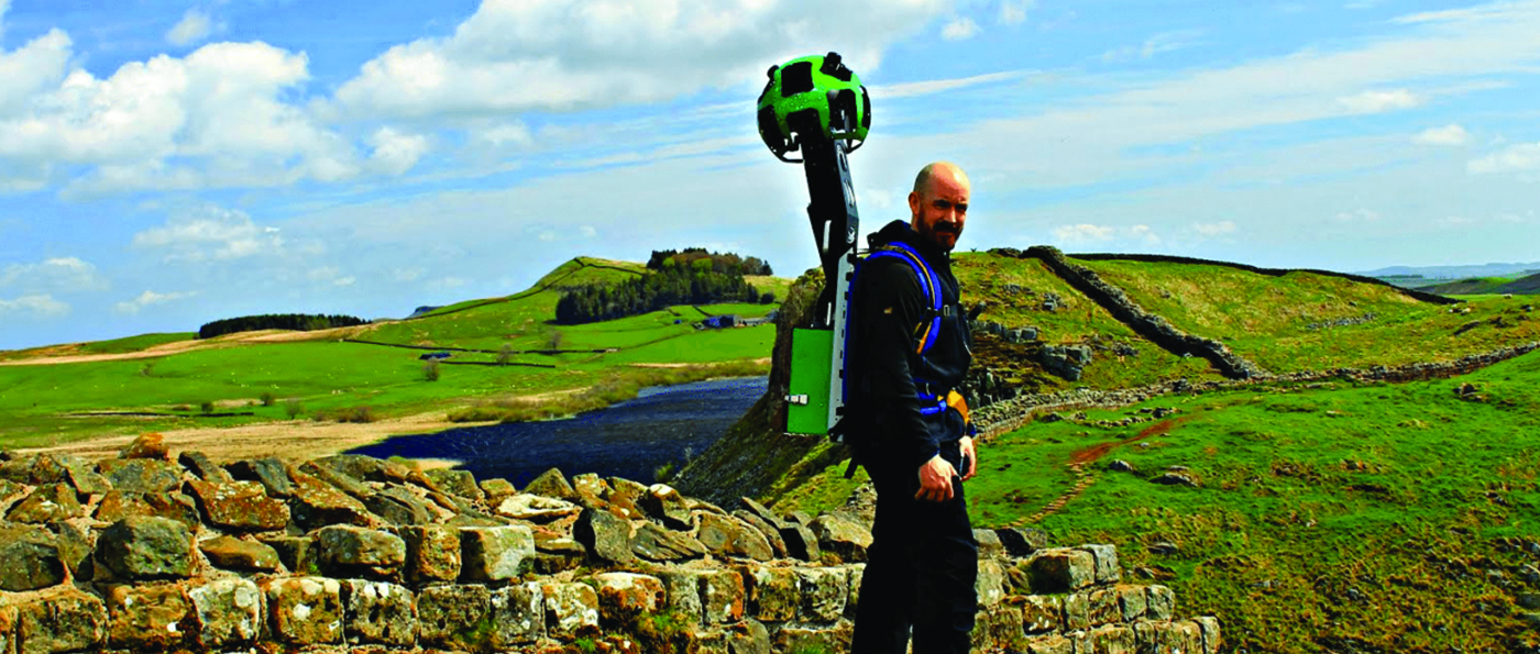 A man carrying a Google backpack stood near to Hadrian's Wall