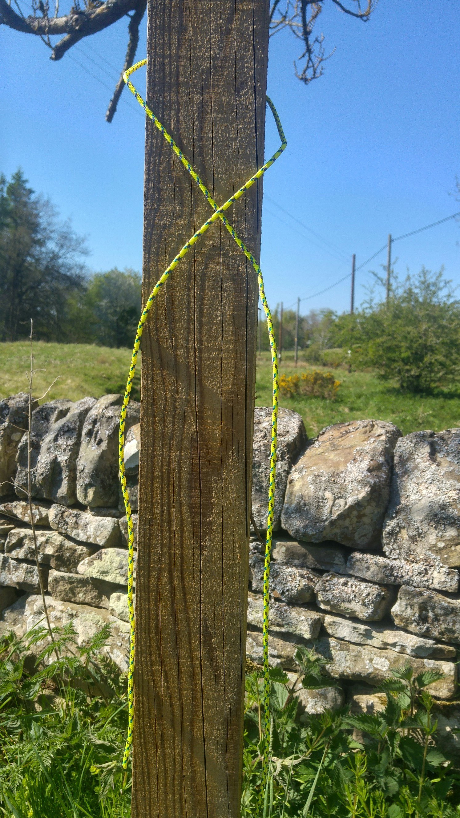 The start of a clove hitch knot around a fingerpost