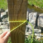 A clove hitch knot being tied around a fingerpost